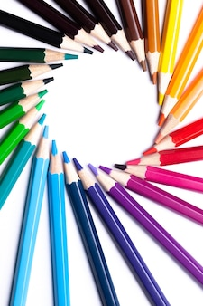 Circle or rainbow swirl of colored pencils on white background, copy space, mock up, lgbt symbol, horizontal.