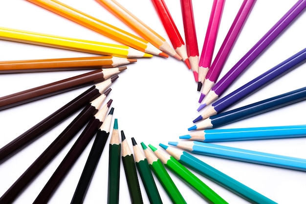 Circle or rainbow swirl of colored pencils on a white background, copy space, mock up, lgbt symbol.