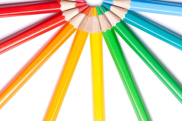 Circle or semicircle of colored sharp pencils spouts in the center on a white isolated background.