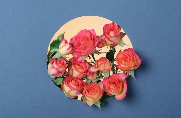 Форма круга вырезана из серой бумаги с красными желтыми розами