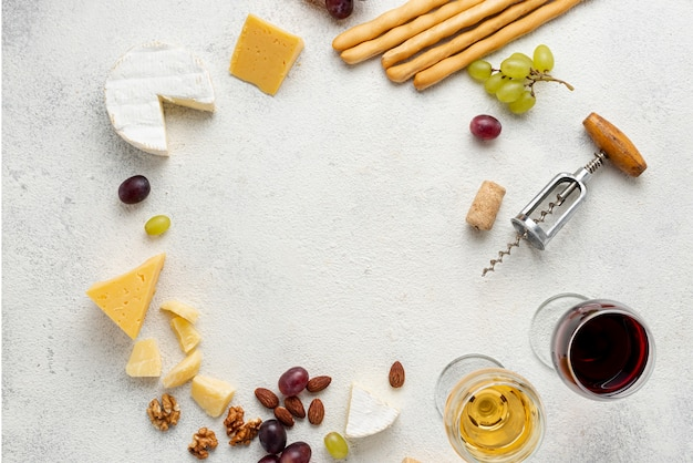 Circle shape formed of wine and cheese on table