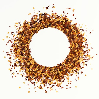 Circle shape frame of crushed red cayenne pepper, dried chili flakes and seeds isolated on a white background