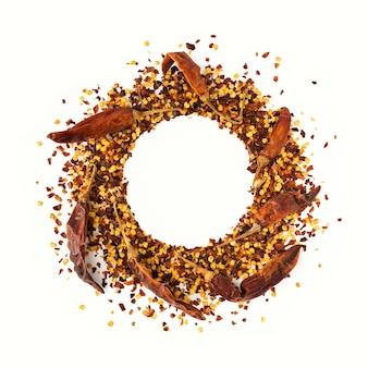 砕いた赤カイエンペッパー、乾燥唐辛子フレーク、白で分離された種子の円形フレーム。料理用の自家製スパイス材料。フードフレームの調味料。
