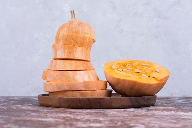 Круглая нарезанная тыква на деревянном блюде посередине, вид сбоку