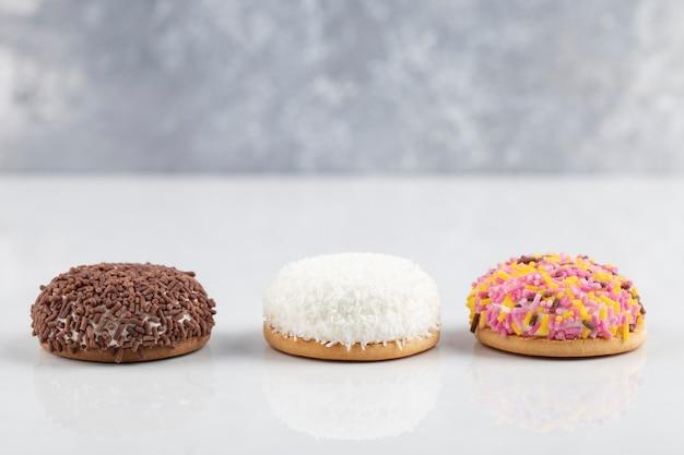 Biscotti marshmallow dolci cerchio con codette su superficie bianca