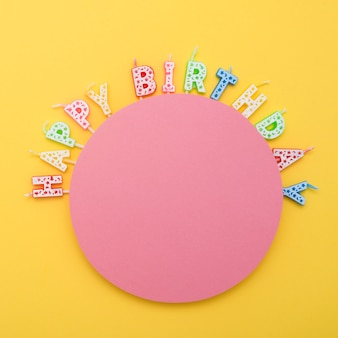Circle of unlit birthday candles with letters