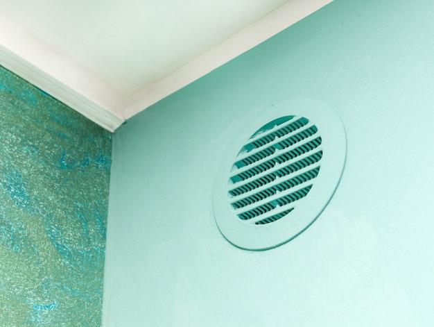 Окно вентиляционного круга на зеленой стене.