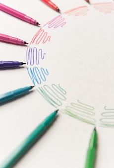白い紙の上のマーカーで描かれた異なるカラフルな紫のストロークのある円。カラフルなストロークのグラデーション。ロゴ、広告用のコピースペース