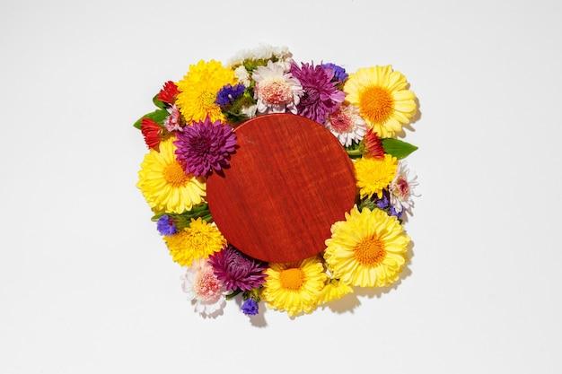 灰色の花のつぼみに囲まれた丸い木の板