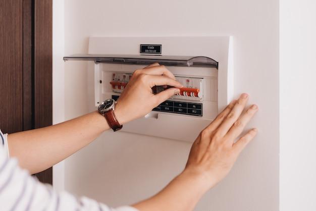 サーキットブレーカボードには多くのスイッチが表示されます。指がそれをオンに戻そうとしています