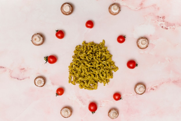 Circular arrangement of green raw pasta; red tomatoes; and mushroom on marble surface