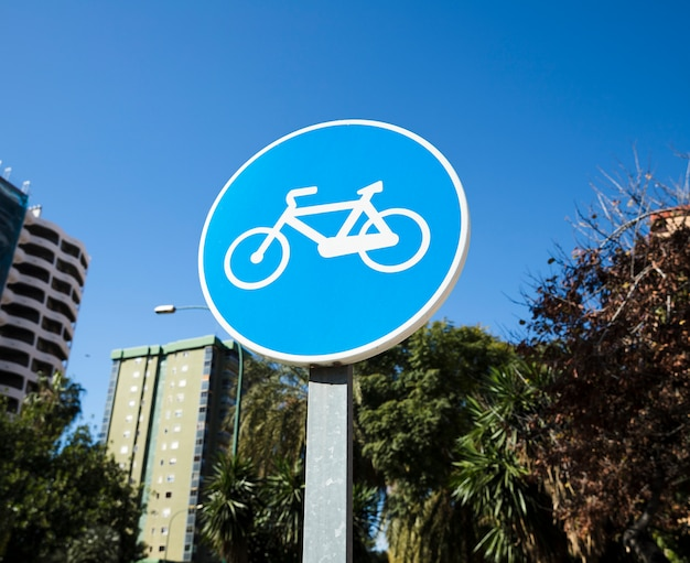 Circular bike path sign against blue sky
