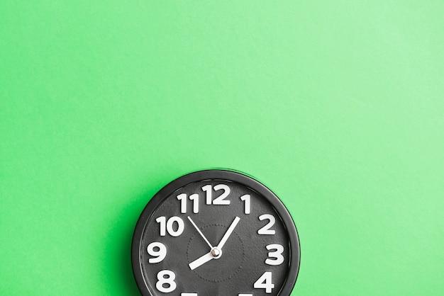 Circular black clock on green wall backdrop