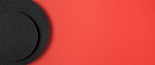 赤い背景の上の円形の黒い紙