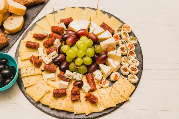 Circular black slate with cheese platter; grapes and smoked sausages on wooden table