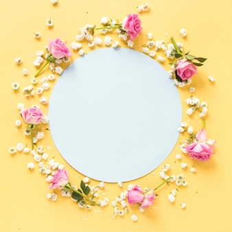 Circular blank frame surrounded with flowers on yellow surface