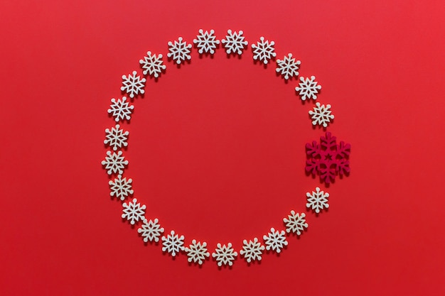 Circular christmas decoration wreath made of white snowflakes on red pink surface