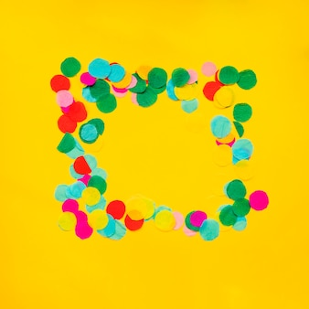 Circular confetti frame border on yellow background
