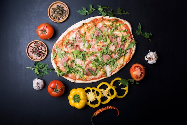 Circular frame made of fresh ingredients around delicious italian pizza over black counter