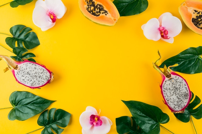 Circular frame made with artificial leaves; orchid flower; papaya and dragon fruits on yellow backdrop