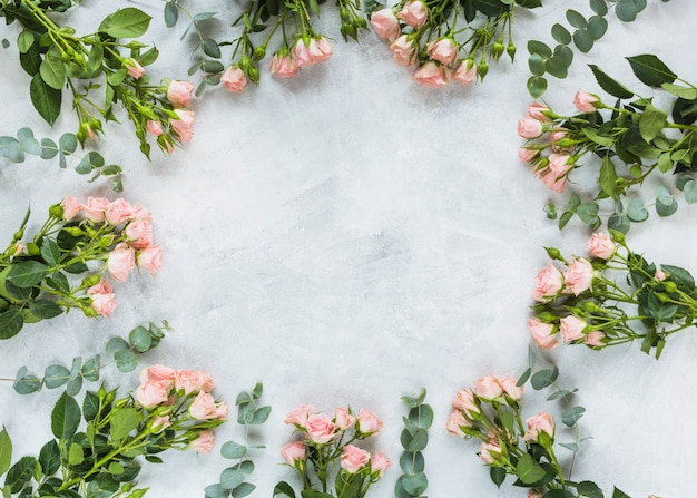 Circular frame made with bunch of roses on concrete background