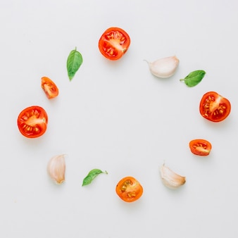 Circular frame made with cherry tomatoes; basil and garlic cloves on white background