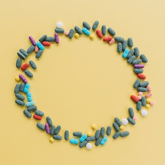 Circular frame made with colorful pills on yellow background
