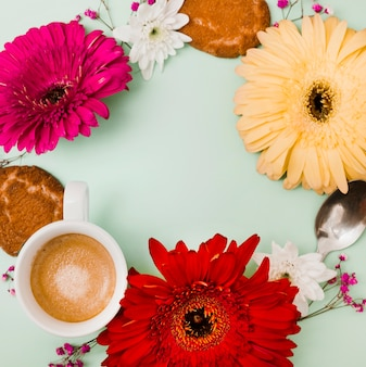 Circular frame made with gerbera flower; coffee cup; spoon and cookies on colored backdrop