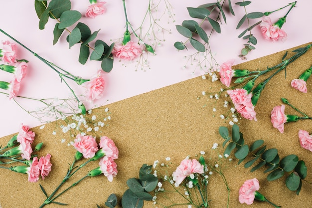 Круглая рамка с гипсофилой и розовыми цветами гвоздики на двойном розовом и картонном фоне