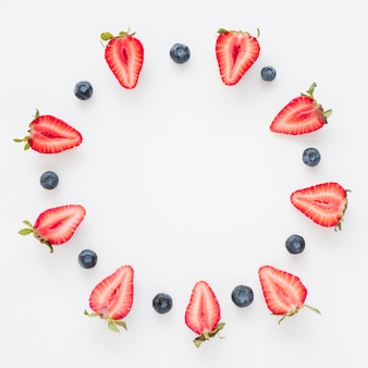 Circular frame made with halved strawberries and blueberries isolated on white background