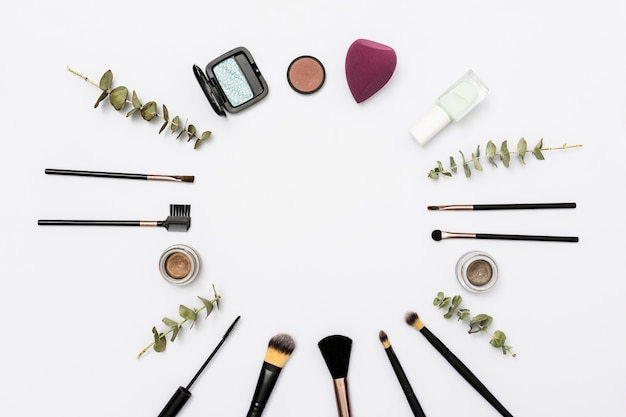 Circular frame made with makeup brushes and cosmetics products on white background