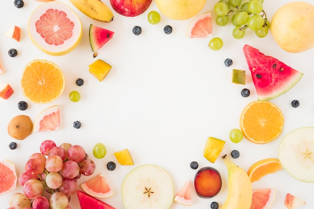Circular frame made with many organic fruits on white backdrop