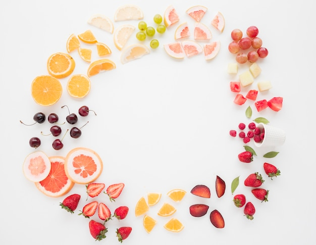 Circular frame made with many slices of fruits on white backdrop