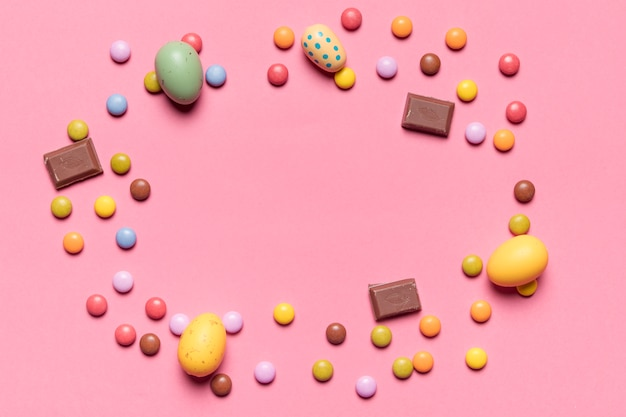 Circular frame made with whole easter eggs and multicolored gem candies on pink background