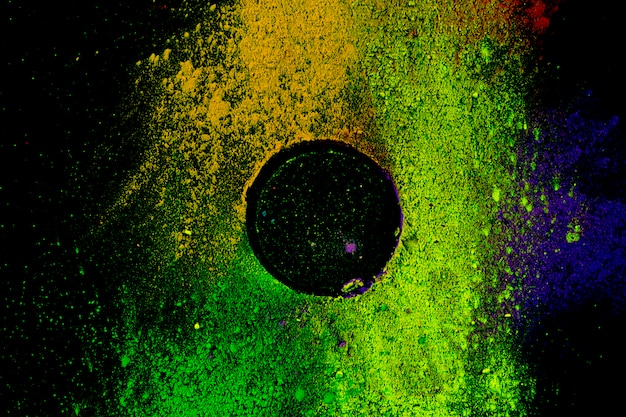 Circular frame of multicolored traditional powder color on black background