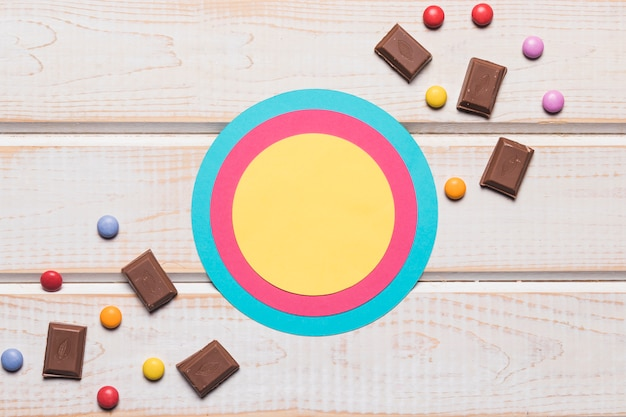 Circular frame with chocolate pieces and gems candies on wooden backdrop