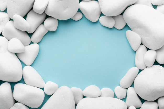 Circular frame with pebbles on blue background