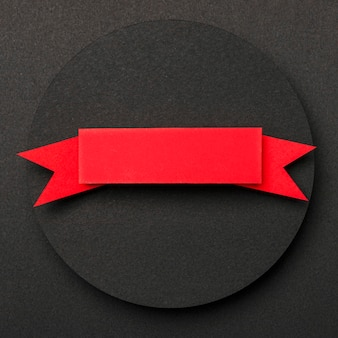 Circular geometric shape of black paper and red ribbon