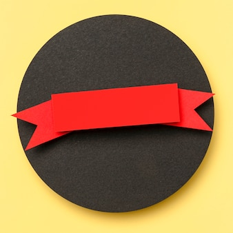 Circular geometric shape of black paper on yellow background