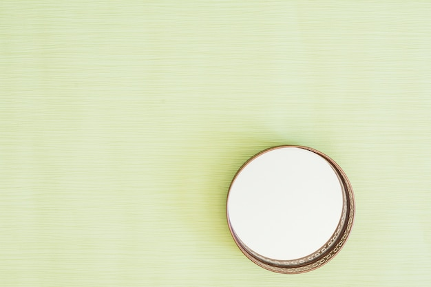 Circular glass mirror on mint green background