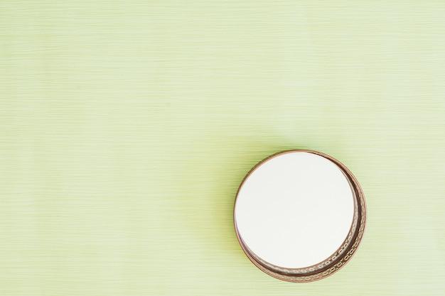 ミントグリーンの背景に円形のガラスミラー