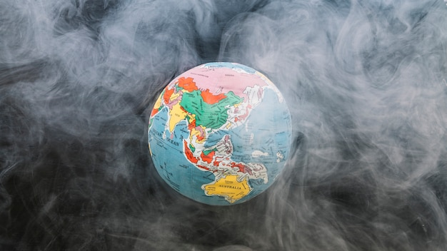 Circular globe surrounded by smoke