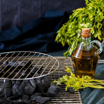 Circular metal sheet on coal with oil bottle and coriander over the table