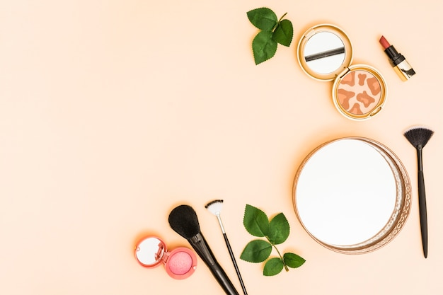 Circular mirror; compact powder; lipstick and makeup brushes with leaves on pastel background