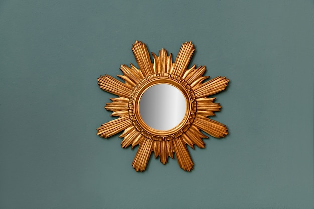 Circular mirror with gilded vintage frame in a star burst pattern hanging on a teal colored wall