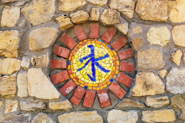 Circular mosaic religious symbol of confucianism on stone wall.