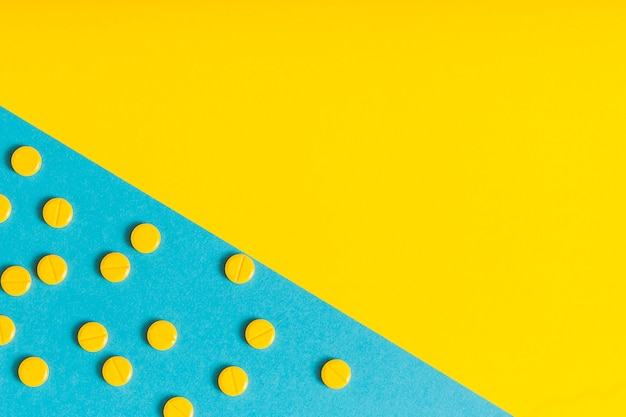 Circular pills on blue and yellow background