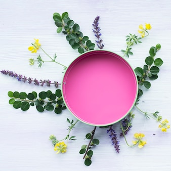 Circular pink empty frame decorated with leaves and flowers on wooden textured background