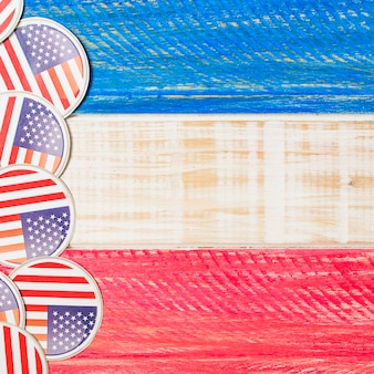Circular usa flag badges on red and blue painted wooden textured desk