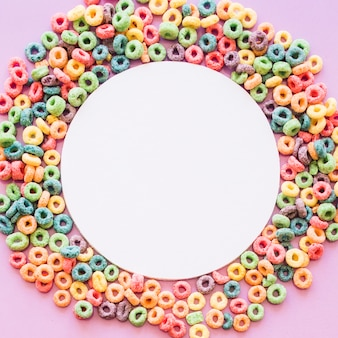Circular white blank frame decorated with colorful cereal loop rings on pink background